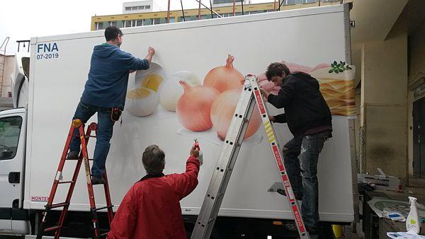 Lidé jak lepí reklamní polep na autě Refi - vejce, cibule, šunka, sýr